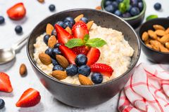 Oatmeal porridge with fresh berries and nuts. Oatmeal cereal porridge with fresh berries and nuts in black bowl. Healthy breakfast. Close up royalty free stock photography