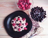 Oatmeal porridge with fresh raspberry and blueberry stock images