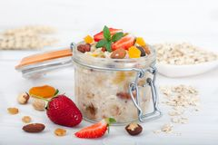 Oatmeal porridge in glass jar with fresh strawberries, nuts and dried fruit. Decorated with mint leaves, white table stock images