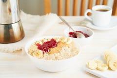 Oatmeal porridge, healthy vegan diet breakfast with strawberry jam, peanut butter, banana, chia on white wooden light background. royalty free stock image