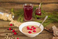 Oatmeal porridge with raspberries and compote on the wooden tabl. Healthy breakfast, Oatmeal porridge with raspberries and beverage Stock Photography