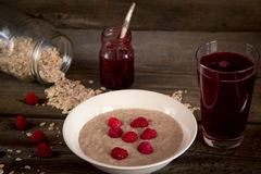 Oatmeal porridge with raspberries and compote on the wooden tabl Royalty Free Stock Photo