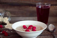 Oatmeal porridge with raspberries and compote on the wooden tabl Stock Image