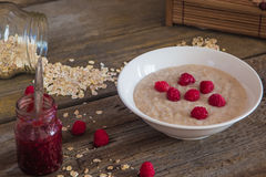 Oatmeal porridge with raspberries and compote on the wooden tabl Royalty Free Stock Photography