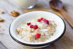 Oatmeal porridge with raspberry and milk, healthy breakfast stock photography