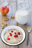 Oatmeal porridge with raspberry and milk, healthy breakfast. Oatmeal porridge with raspberries, walnuts, red apple and milk on textured wooden table, country Royalty Free Stock Images