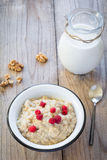 Oatmeal porridge with raspberry and milk, healthy breakfast. Oatmeal porridge with raspberries, walnuts, red apple and milk on textured wooden table, country Stock Images