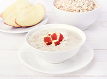Oatmeal porridge with red apple slices Royalty Free Stock Photography