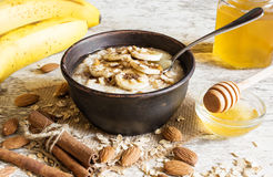 Oatmeal porridge with a spoon in ceramic bowl. healthy breakfast Stock Photo
