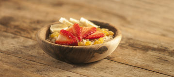 Oatmeal porridge with strawberry and banana in wood bowl Royalty Free Stock Images