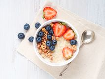 Oatmeal porridge with strawberry, blueberry, granola on white wooden background. Healthy breakfast. Top view royalty free stock images