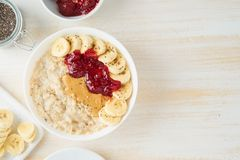 Oatmeal porridge with strawberry jam, peanut butter, banana. Top view, copy space on white wooden light background, healthy vegan royalty free stock photos