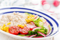 Oatmeal porridge with vegetable salad of fresh tomatoes, corn, cucumber and lettuce. Light, healthy and tasty dietary breakfast. Oatmeal porridge with vegetable royalty free stock photos