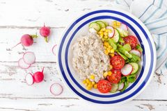 Oatmeal porridge with vegetable salad of fresh tomatoes, corn, cucumber and lettuce. Light, healthy and tasty dietary breakfast. Top view stock photo