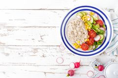Oatmeal porridge with vegetable salad of fresh tomatoes, corn, cucumber and lettuce. Light, healthy and tasty dietary breakfast. Top view stock photography