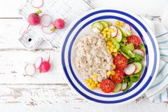 Oatmeal porridge with vegetable salad of fresh tomatoes, corn, cucumber and lettuce. Light, healthy and tasty dietary breakfast. Top view royalty free stock images