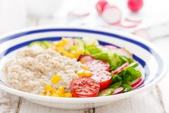 Oatmeal porridge with vegetable salad of fresh tomatoes, corn, cucumber and lettuce. Light, healthy and tasty dietary breakfast. Or lunch stock images