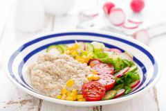 Oatmeal porridge with vegetable salad of fresh tomatoes, corn, cucumber and lettuce. Light, healthy and tasty dietary breakfast. Or lunch stock photo