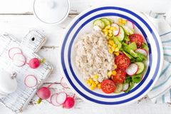 Oatmeal porridge with vegetable salad of fresh tomatoes, corn, cucumber and lettuce. Light, healthy and tasty dietary breakfast. Top view royalty free stock photography