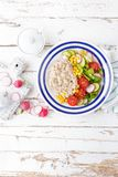 Oatmeal porridge with vegetable salad of fresh tomatoes, corn, cucumber and lettuce. Light, healthy and tasty dietary breakfast. Top view stock images