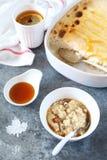 Oatmeal pudding with raisins and cinnamon, maple syrup dressing. And lemon tea stock photos