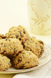 Oatmeal raisin chocolate chip cookies. Fresh baked oatmeal raisin chocolate chip cookies on pale yellow background in vertical format with room for copy Royalty Free Stock Photos