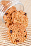 Oatmeal raisin cookies coming out of a glass jar. Freshly delicious baked oatmeal raisin cookies coming out of a glass jar on a wooden background Stock Images