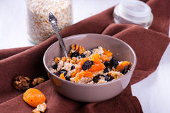 Oatmeal with raisins, dried apricots, plums in the bowl Stock Photos