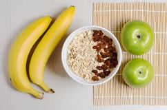 Oatmeal with raisins on the tablecloth from bamboo. Two bananas stock images