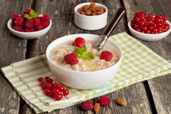 Oatmeal with raspberries and honey. Horizontal, close up Royalty Free Stock Photos