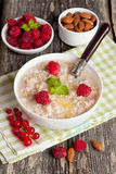 Oatmeal with raspberries and honey. Vertical, close up Royalty Free Stock Photo