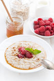 Oatmeal with raspberries and honey, vertical Stock Image