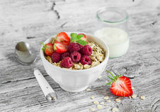 Oatmeal with raspberries, strawberries and natural yoghurt in a bowl Stock Photo