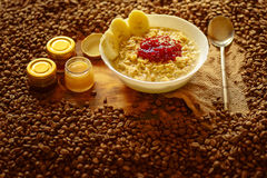 Oatmeal with raspberry jam, honey and coffe beans Royalty Free Stock Photography