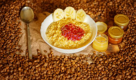 Oatmeal with raspberry jam, honey and coffe beans Royalty Free Stock Images