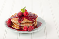 Oatmeal Raspberry Pancakes side view. Side view on white background - Whole wheat oatmeal pancakes with boysenberry sauce topped with red raspberries and a mint royalty free stock photos