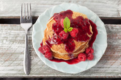 Oatmeal Raspberry Pancakes top view. Top view - Whole wheat oatmeal pancakes with boysenberry sauce topped with red raspberries and a mint sprig on a weathered stock photos