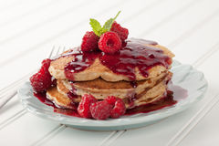Oatmeal Raspberry Pancakes whole wheat. Whole wheat oatmeal pancakes with boysenberry sauce topped with red raspberries and a mint sprig on white wood stock images