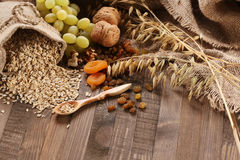 Oatmeal in a sac, ears of oats, dried apricots, raisins, grapes, Royalty Free Stock Photo