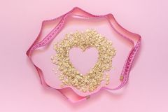 Oatmeal in shape of heart and turn round measuring tape on pink background. Diet concept stock photo