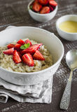 Oatmeal with strawberries and honey in a white bowl Stock Photography