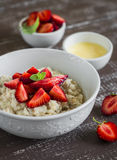 Oatmeal with strawberries and honey in white bowl Stock Photography