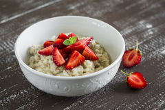 Oatmeal with strawberries in a white bowl Stock Photography
