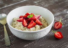 Oatmeal with strawberries in a white bowl Royalty Free Stock Photo