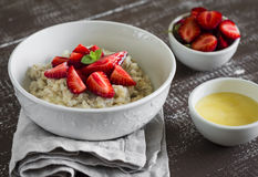 Oatmeal with strawberries in a white bowl Royalty Free Stock Photos