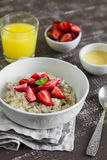 Oatmeal with strawberries in a white bowl and orange juice Stock Photo