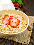Oatmeal with strawberry on board Royalty Free Stock Image