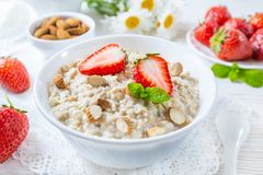 Oatmeal with strawberry and nuts in bowl on white wooden table stock images