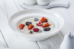 Oatmeal with strawberry and raspberry in a bowl stock photos