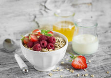 Oatmeal with summer berries - raspberries, strawberries, honey and yogurt in a white bowl. On a light wooden background stock image